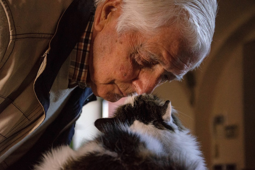 A man touching noses with his cat